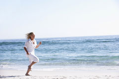 Senior Woman Running along Sandy Beach Stock Photo