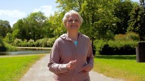Senior woman running along summer park stock video footage