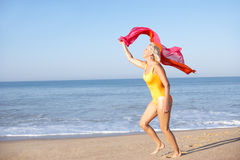 Senior woman running on beach Royalty Free Stock Photos