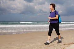 Senior Woman Running On the Beach Stock Photo