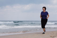 Senior Woman Running On the Beach Stock Image