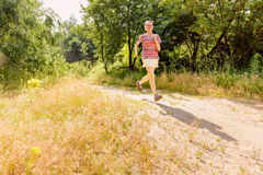 Senior Woman Running in the Forest Stock Image