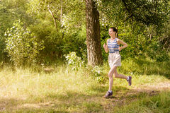 Senior Woman Running in the Forest Stock Images
