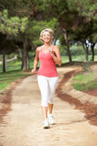 Senior woman running in park Stock Image