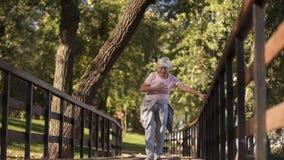 Senior woman running in park, suffering heartache, health problem in elder age. Stock photo royalty free stock photo