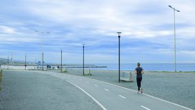 Senior woman running in a promenade against a blue cloudy sky. Active ageing concept and empty copy space stock images