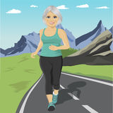 Senior woman running or sprinting on road in mountains. Fit mature female fitness runner during outdoor workout. Senior woman running or sprinting on the road in Stock Photo