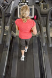 Senior woman running on treadmill in health club Stock Images