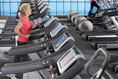 Senior woman running on treadmill in health club Royalty Free Stock Photos