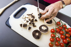 Senior woman's hand chopping mushrooms on cutting board Stock Images