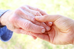 Senior woman's hand and helping hand Stock Photos