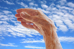 Senior woman's hand over sky Stock Photo