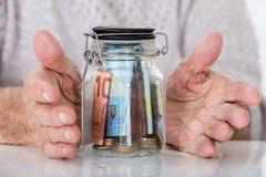 Senior Woman`s Hand Protecting Money Jar stock photos