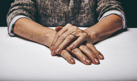 Senior woman's hands clasped on a table Royalty Free Stock Photos