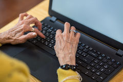 Senior woman`s hands and laptop. Stock Image
