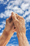 Senior woman's hands over sky Stock Image