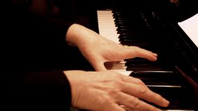 Senior woman`s hands playing piano. Close up side view of elderly hands and fingers playing a song. Senior woman`s hands playing piano. Close up side view of