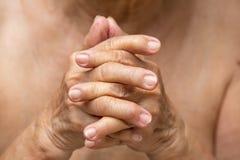 Senior woman`s hands praying, Body language feeling stock photography