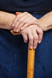 Senior woman's hands on wooden walking stick. Closeup of senior woman's hands on wooden walking stick Royalty Free Stock Photo