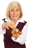 Senior woman saving money in piggybank. Senior smiling woman saving money and putting coin in a gold piggy bank isolated on white background Royalty Free Stock Photo