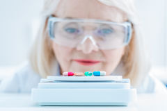 Senior woman scientist looking at pills on lab scales Stock Photos