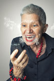 Senior woman screaming angry at phone Royalty Free Stock Images