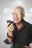 Senior woman screaming angry at phone Stock Photo