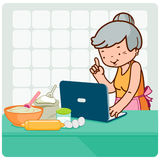 Old woman searches recipes on the internet Stock Image