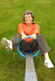 Senior woman on seesaw Royalty Free Stock Photo