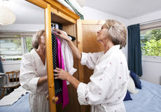 Senior woman selecting clothes from closet at home Stock Images