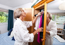 Senior woman selecting clothes from closet at home Royalty Free Stock Photo