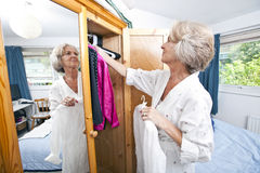 Senior woman selecting dress from closet at home royalty free stock image