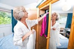Senior woman selecting dress from closet at home Stock Photo