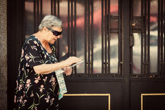 Senior Woman Selling Lottery Coupons in the Street Stock Photography