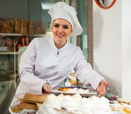 Senior woman selling pastry. Smiling young woman with hat posing in bakery near pastry stock images