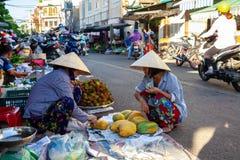 A senior woman sells papaya at the street market stock photo