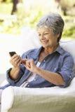 Senior Woman Sending Text Message Sitting On Sofa Stock Photos