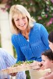 Senior Woman Serving A Family Meal. Senior Woman Serving At Multi Generation Family Meal Stock Photography