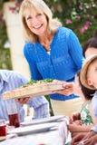 Senior Woman Serving A Family Meal. Senior Woman Serving At Multi Generation Family Meal Royalty Free Stock Photos