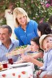 Senior Woman Serving A Family Meal. Senior Woman Serving At Multi Generation Family Meal Outside Royalty Free Stock Photos