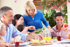 Senior Woman Serving A Family Meal. Senior Woman Serving At Multi Generation Family Meal Royalty Free Stock Image