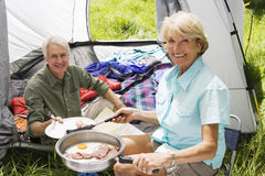 Senior woman serving husband fried breakfast on camping trip, man sitting inside tent, smiling, portrait Royalty Free Stock Photo