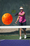 Senior Woman Serving Pickleball Stock Photo