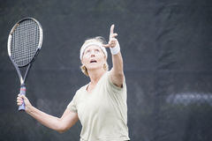 Senior woman serving at tennis Royalty Free Stock Image