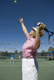 Senior Woman Serving Tennis Ball Royalty Free Stock Photography