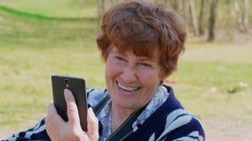 Senior woman setting hair on video call via mobile, talking stock video