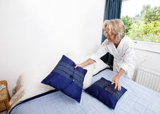 Senior woman setting up cushions on bed at home Royalty Free Stock Photography