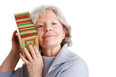 Senior woman shaking a gift stock images
