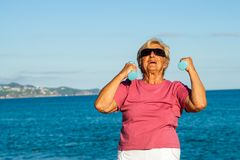 Senior woman shaping up on beach. Royalty Free Stock Photos