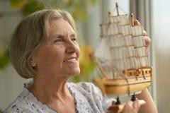 Senior woman with ship Stock Photos